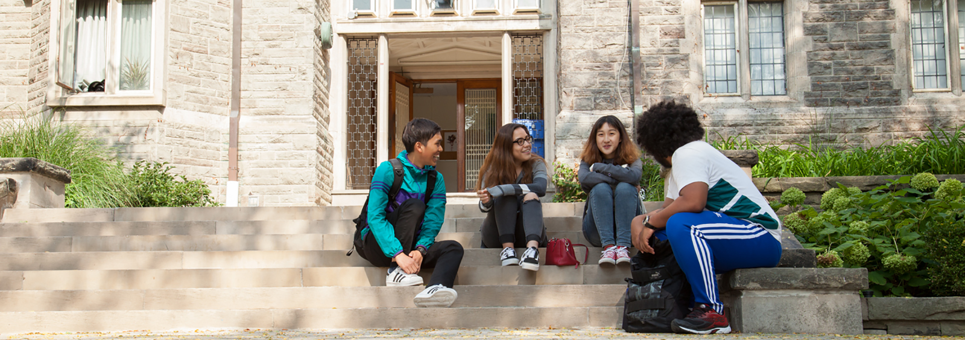 Students sitting on the stone steps in the Quad