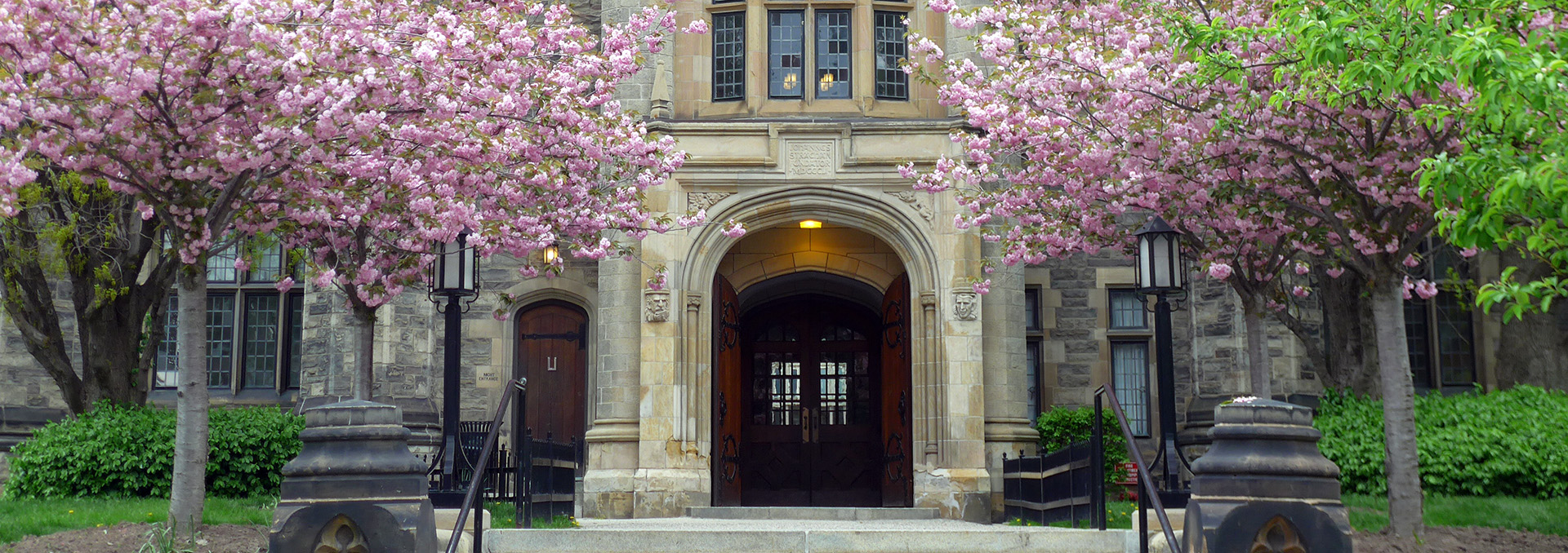 Front entrance to Trinity College with pink crabapple blossoms