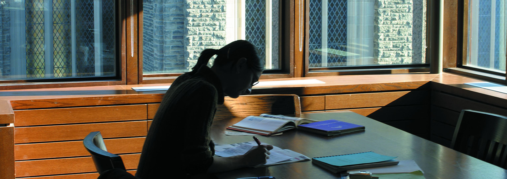 Student studying at a table in the John W Graham Library