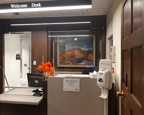Welcome Desk with Plexiglas barrier, signage and sanitizer dispenser