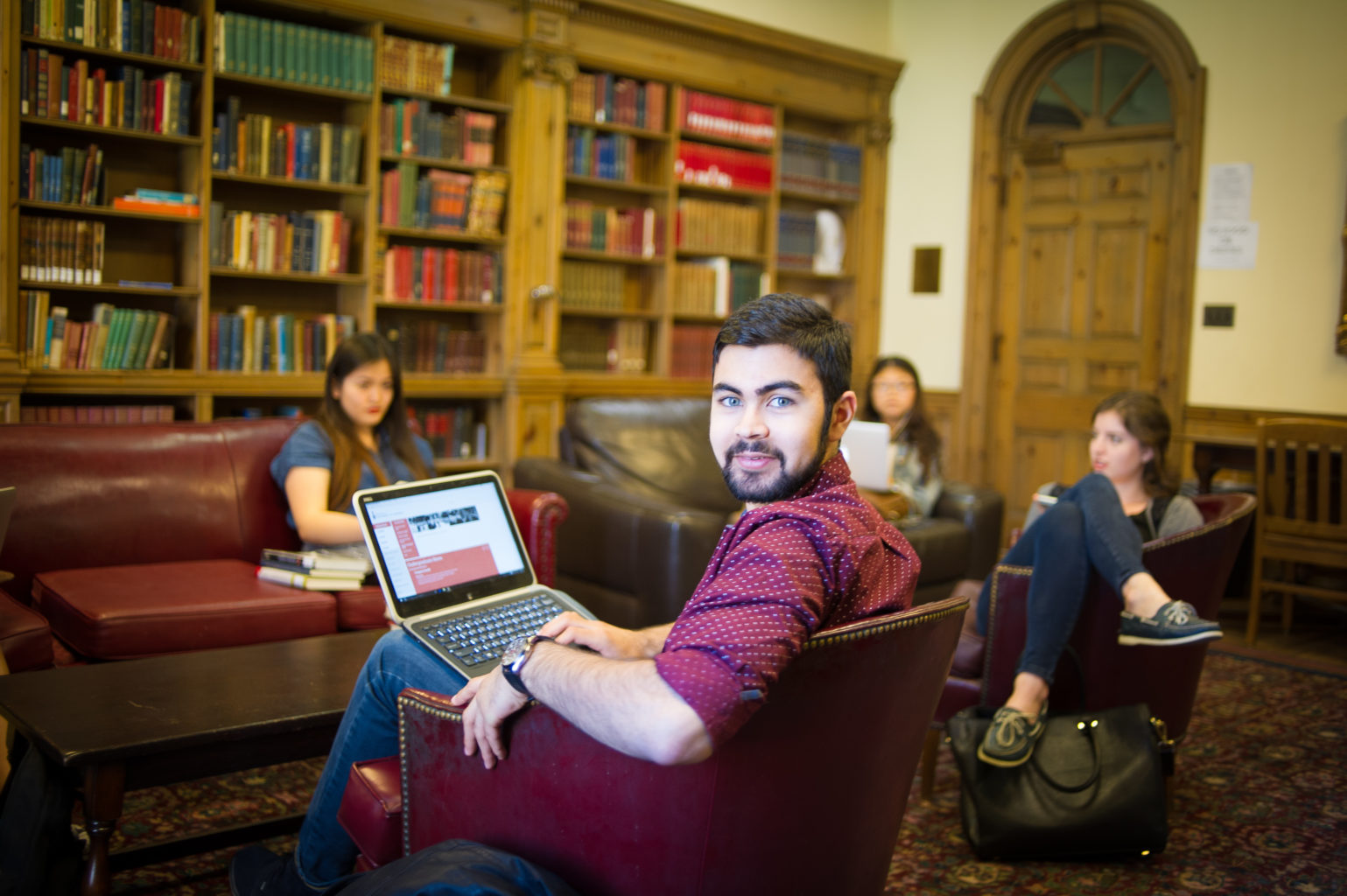 Student looks at the camera while other students are studying in the Stedman Library in St. Hilda's College