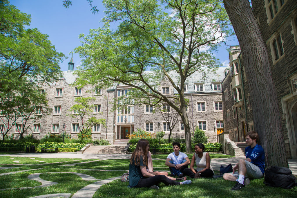 Students sitting under a tree in the Trinity College Quadrangular